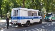 Einsatzfahrzeuge der Polizei stehen in Berlin-Moabit unweit des Tatorts, an dem ein Fahrradfahrer einen Mann erschossen haben soll.