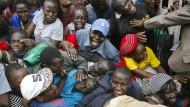 Bewohner drängen in Nairobi durch ein Tor, während einer geplanten Verteilung von Nahrungsmitteln für Menschen im Zuge der Corona-Pandemie.