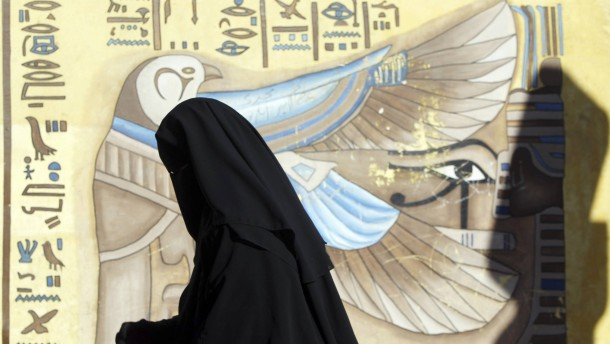 A woman wearing a full veil queues near a hieroglyphic mural outside a polling centre as she waits to vote in Egypt