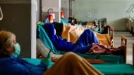 In Brescia liegen die Patienten mit Mundschutzmasken in einer Bettenreihe und halten über Smartphones Kontakt mit ihren Familien.
