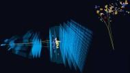 Schnitt durch den LHCb-Detektor: Von links ankommende geladene B-Mesonen  zerfallen auf ihrem Flug. Die Zerfallsprodukte werden in den verschiedenen  Sensoren (blaue Schichten) registriert und vermessen.