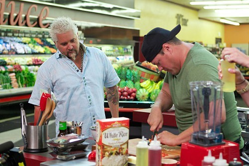 Guy Fieri works with a comptitor on Guys Grocery Games