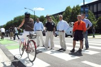 Mayor Rahm and fellow politicians watch bikers ride by.