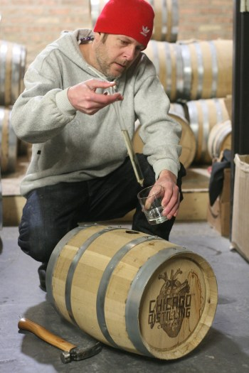 Vince DiPrizio pulling hte first of the vodka out of the barrel