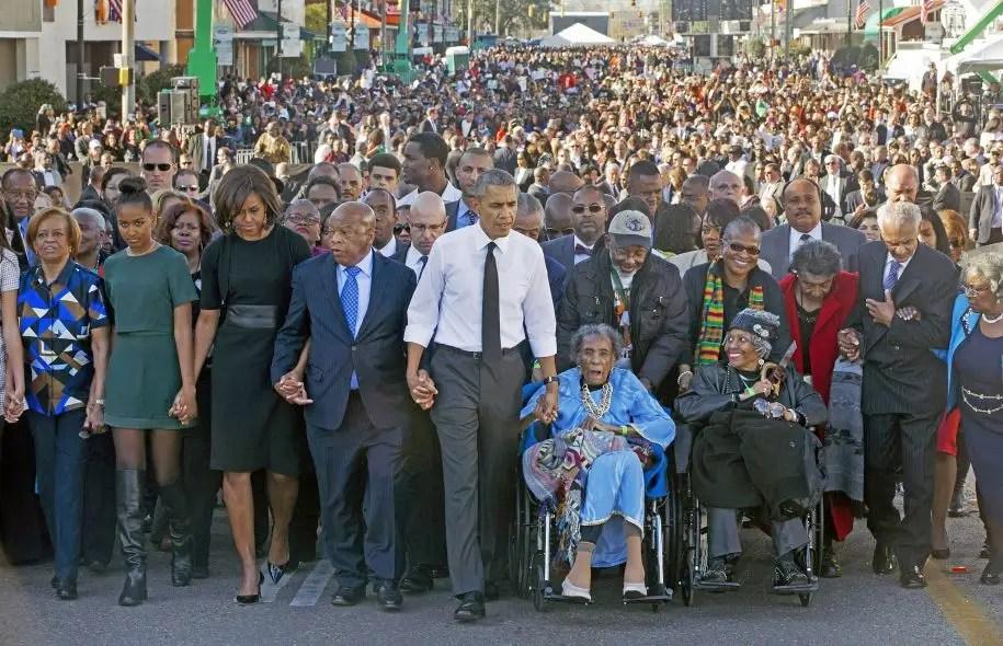 De passage dans la petite ville de Selma, samedi, pour souligner les cinquante ans d'une marche pour les droits civiques au cours de laquelle les forces de l'ordre avaient chargé quelque 600 manifestants, le «Bloody Sunday», Barack Obama (au centre), accompagné de sa famille, a marché auprès d'Amelia Boynton Robinson, battue lors des affrontements.