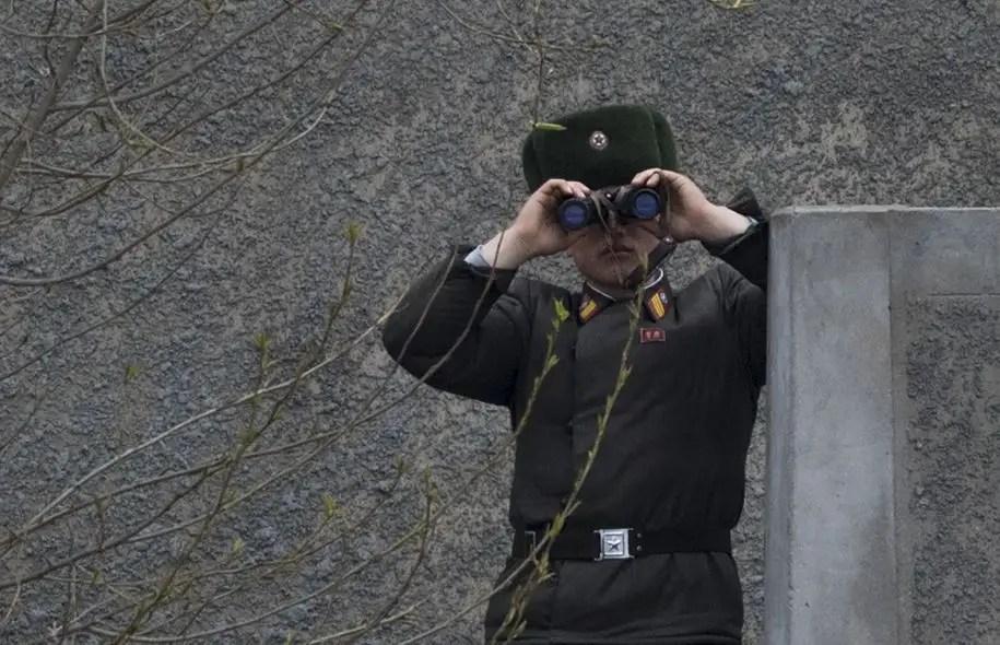 Un soldat nord-coréen utilise ses jumelles pour observer de l'autre côté de la rivière Yalu, près de Sinuiju, en face de la ville frontalière chinoise de Dandong.