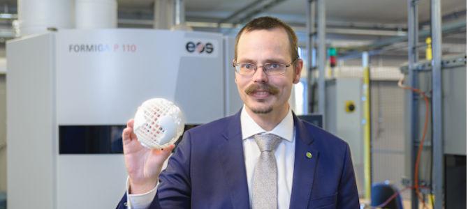 Max Andersson står framför en 3D-skrivare, och håller upp en 3D-printad jordglob.