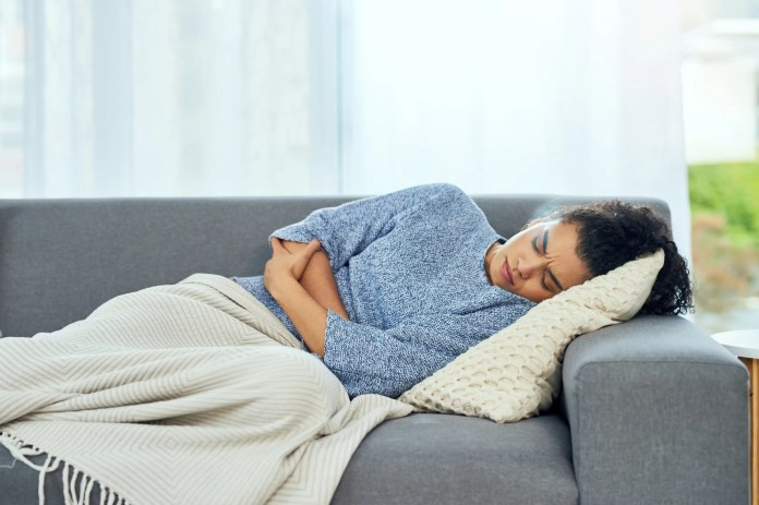 Shot of a young woman experiencing stomach pain on the sofa at home