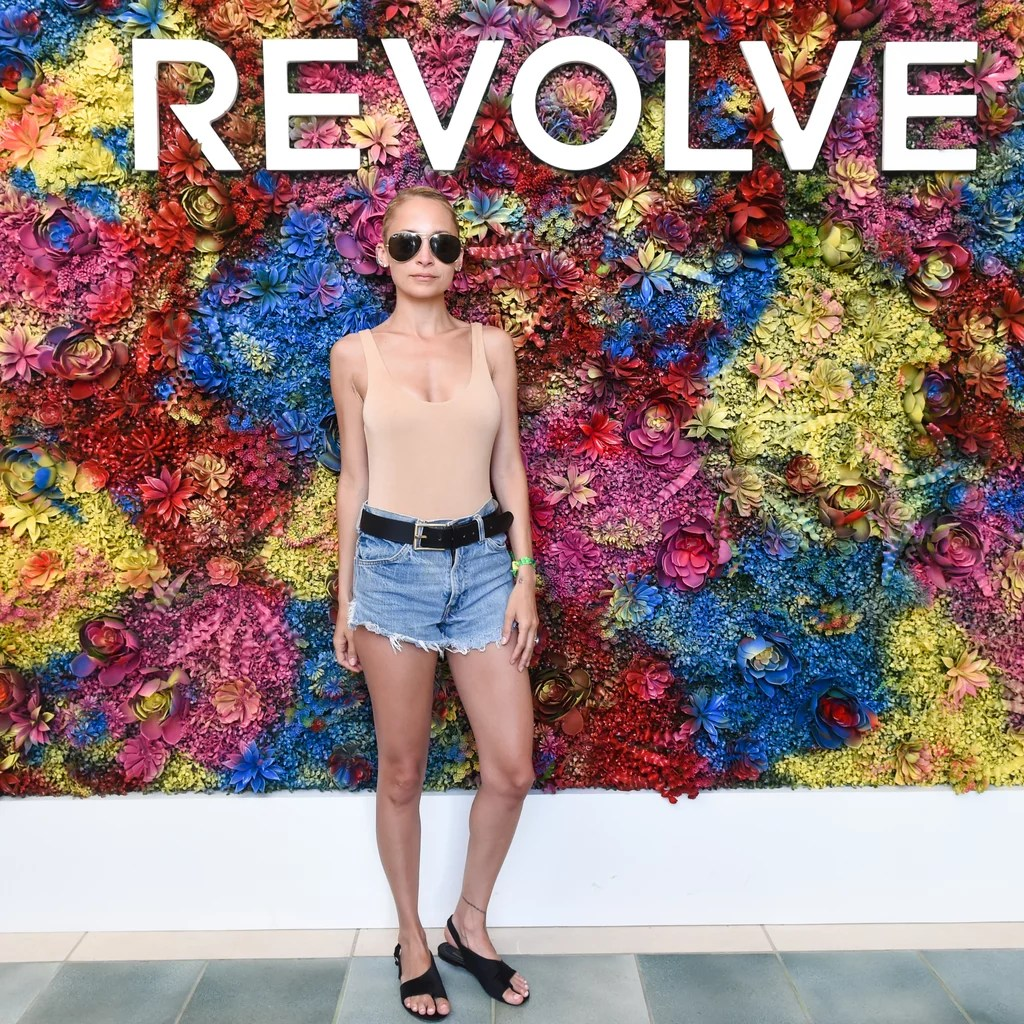 Nicole Richie wearing a sleek tank, denim shorts, and flat sandals at the Revolve Festival party.