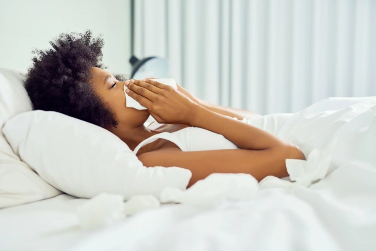 Cropped shot of an attractive young woman blowing her nose and lying in bed at home