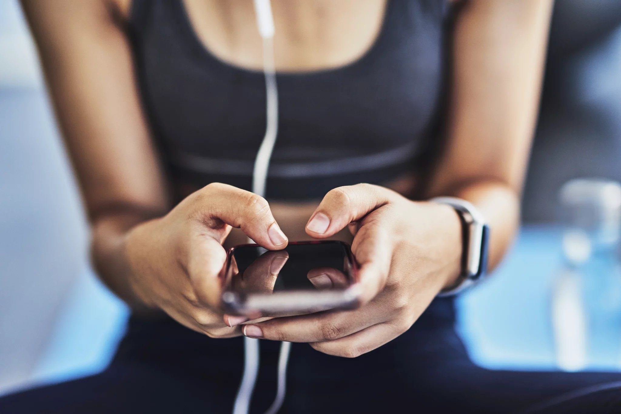 Closeup shot of a sporty woman using a cellphone while exercising in a studio