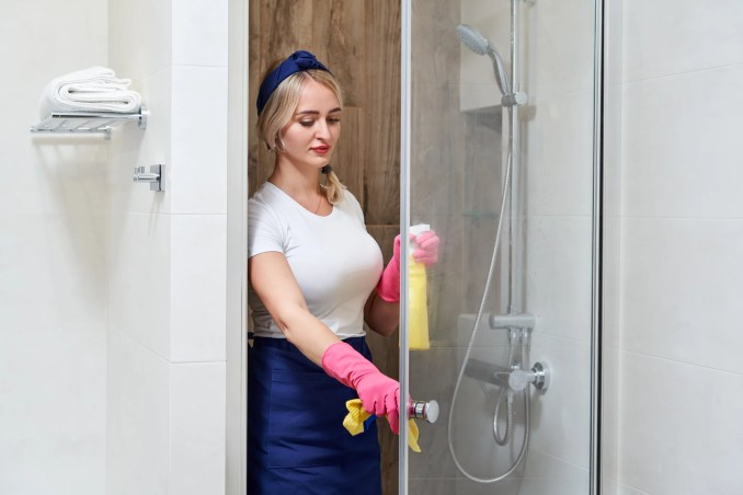 Young beautiful woman cleaning glass shower cabin with sponge and spray bottle