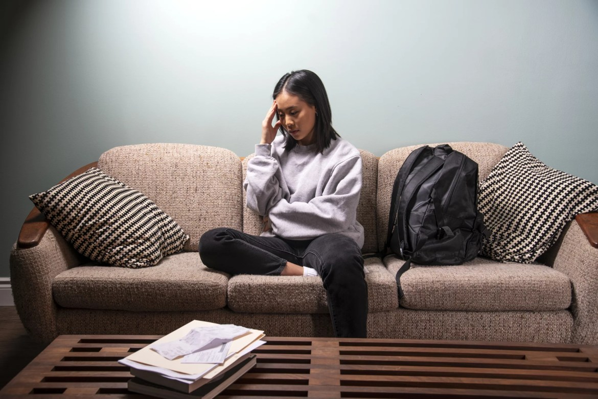 A university student of Asian heritage experiencing financial or emotional stress at home in her apartment.