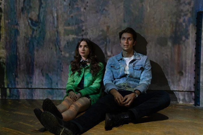 EMILY IN PARIS (L to R) LILY COLLINS as EMILY and LUCAS BRAVO as GABRIEL in episode 105 of EMILY IN PARIS Cr. STEPHANIE BRANCHU/NETFLIX  2020