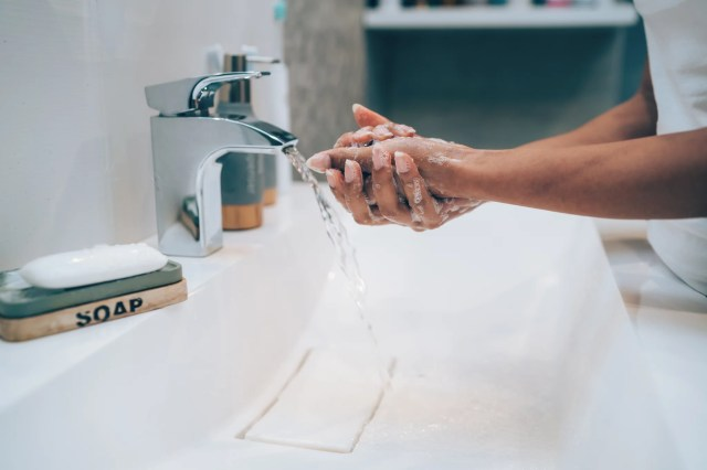 Cropped shot of an unrecognizable woman washing her hands in the bathroom at home