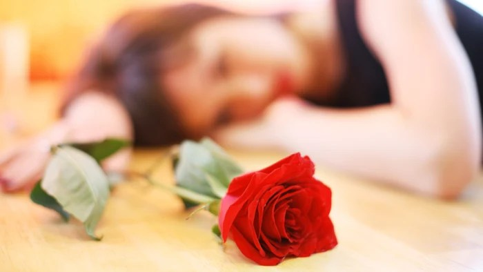 Lonely young woman with red rose