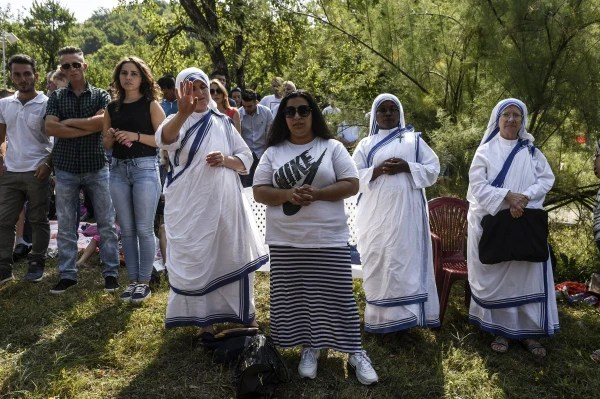 Image: Pilgrims pray near the church in the village of Letnica