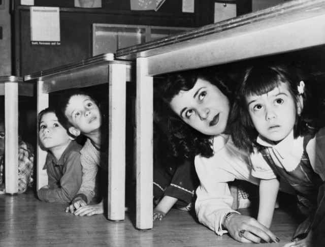 Teacher And Children Crouching Under Table