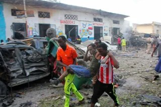Image: Somalis carry away a man injured after a car bomb was detonated