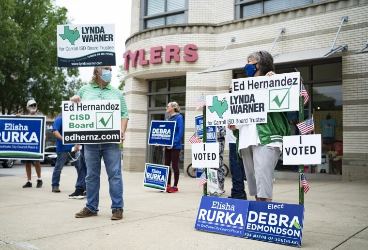 People hold campaign signs for various candidates in municipal elections in Southlake, Texas, on May 1, 2021.