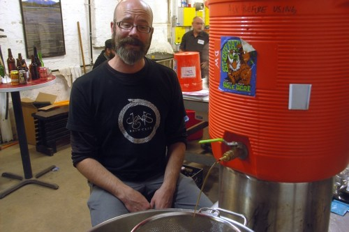 Board member Steven Lane transfers his imperial stout from a mash tun to a brew kettle. That skeptical look is for me, not for the beer.