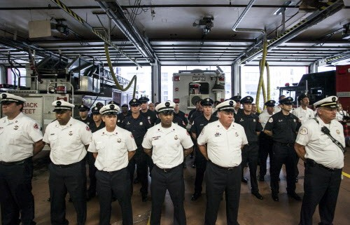 Firefighters stand at attention for a roll call during an open house celebration for the 100th anniversary of Chicago Fire Departments Squad 1.