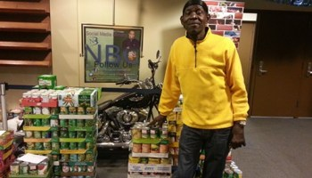 Frank Tooley, who does odd jobs at New Beginnings Church, stands in the church lobby just after a poll closed in the lobby Tuesday. Behind him are canned goods the church is collecting for a Thanksgiving food drive, and a motorcycle it will auction off to raise money for a community center across the street.