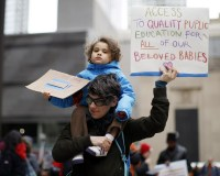 Robin DAverso, a charter school teacher, carries her daughter Zahraa Raven, 4, during a rally in opposition to the plan to close public schools in Chicago.