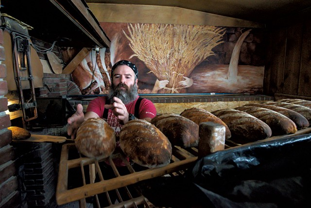 Trent Cooper puts a freshly baked leavened bâtard on a cooling rack in Westford - GLENN RUSSELL
