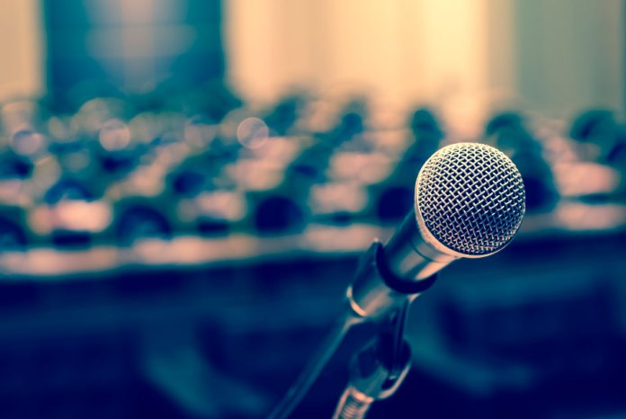 microphone on a dais in front of a room of empty seats