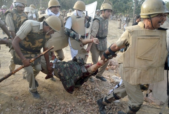 Indian police carry a colleague injured during clashes with members of a sect said to have been living illegally at the Jawahar Bagh park in Mathura on June 2, 2016. Clashes between Indian police and followers of a revolutionary sect have left at least 23 people dead after an operation to evict thousands of people from parkland erupted into violence, officials said June 3. Two police officers were among those killed in the overnight clashes during a move to expel around 3,000 sect followers who had illegally occupied public land in the city of Mathura for the last two years. / AFP PHOTO / STR