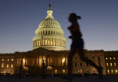 Image: A jogger runs by as night falls on the U.S. Capitol on the eve of a potential government shutdown.