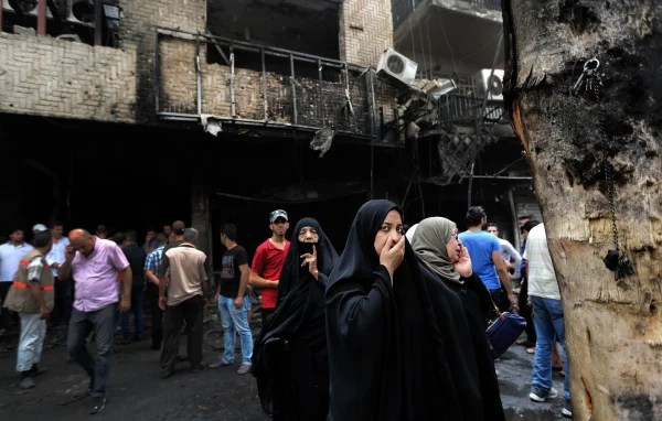 Image: Iraqi women wait to hear about family members who went missing after a car bomb hit Karada