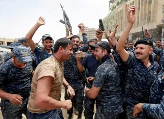 Image: Iraqi police celebrate gains in Mosul, Saturday.