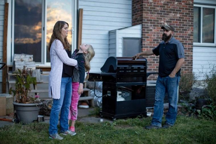 Kristen Kilmer with her daughter and her husband, Chet Kilmer, outside their home.