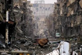 Image: Syrians walk along a severely damaged road