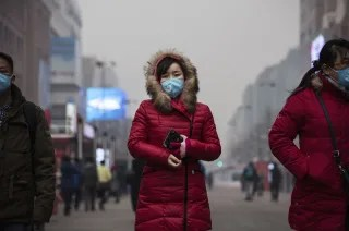Image:  A Chinese woman wears mask to protect agains pollution as she walks through a shopping area in heavy smog on December 8, 2015 in Beijing, China.
