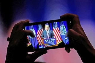 A supporter photographs Republican U.S. Presidential nominee Donald Trump during a campaign event at Briar Woods High School in Ashburn