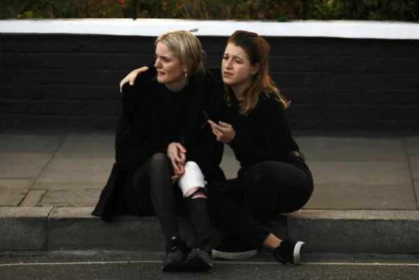 Image: An injured woman reacts outside Parsons Green tube station in London