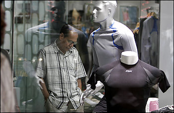 A man window-shops outside a store at Forum Mall, the oldest shopping mall in Bangalore. A retail survey taken at malls across the country this month reported a 22 percent decrease in buying compared with the previous three months.