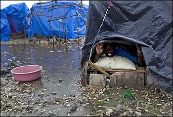 A man looks from inside his tent at a homeless earthquake survivors camp during heavy rains in Port-au-Prince, Friday, March 19, 2010. A 7.0-magnitude earthquake hit Haiti on Jan. 12, killing and injuring thousands and leaving more than a million people living in makeshift camps. (AP Photo/Ramon Espinosa)