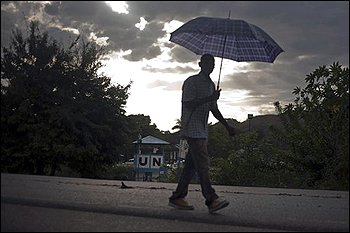 A man walks with an umbrella by Nepal's U.N. base in Mirebalais, Haiti, Sunday Oct. 31, 2010. A cholera outbreak that has killed more than 300 people in Haiti matches strains commonly found in South Asia, the U.S. Centers for Disease Control and Prevention said Monday, intensifying the scrutiny of a U.N. base that is home to recently arrived Nepalese peacekeepers, built on a tributary to the Artibonite River. (AP Photo/Ramon Espinosa)