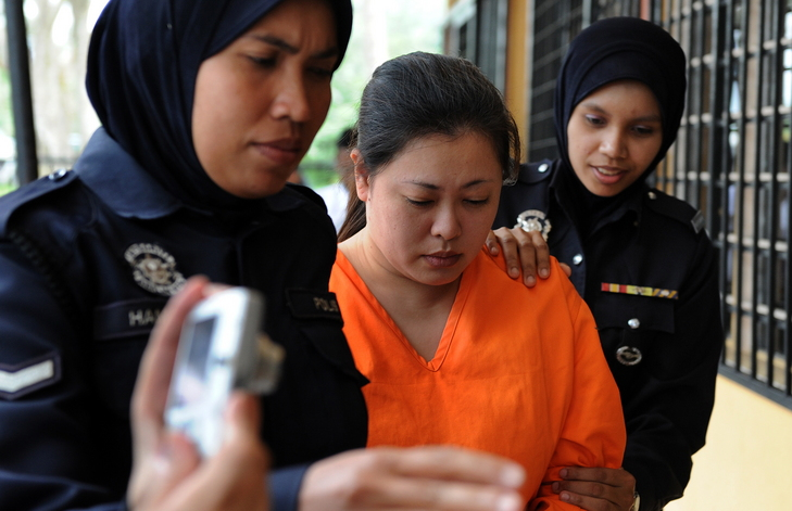 Police woman escorting the accused, now convicted, Takeuchi