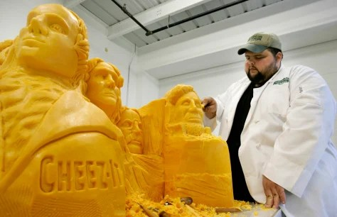 Man carves cheese and looks like he enjoys it