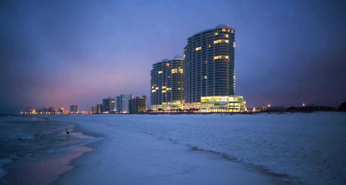 Image: The Turquoise Place condominium buildings rise above Orange Beach, Alabama, before sunrise.