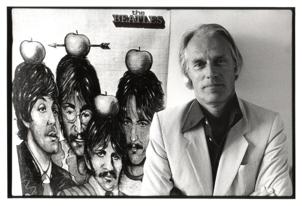 Image: George Martin poses next to a poster of the Beatles
