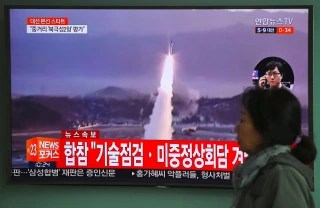 Image: A woman walks past a television screen showing file footage of a North Korean missile launch