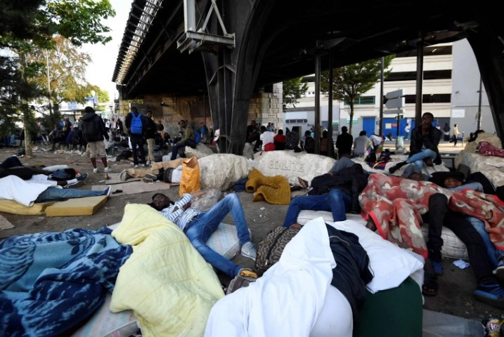 Thousands Evicted from Paris Migrant Camp Image  Migrants and refugees rest on the ground