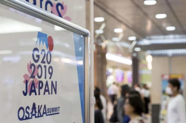 Image: A sign for the G-20 Summit at a train station on June 26, 2019 in Osaka, Japan.