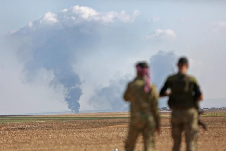 Image: Turkey-backed Syrian fighters watch as smoke billows in the distance during clashes between Syrian regime forces, and Turkish forces, 15kms east of the northeastern town of Ras al-Ein